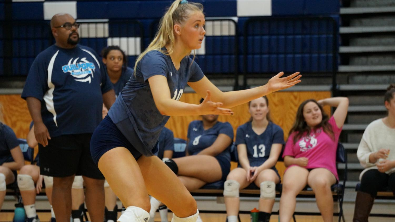 Eye of the Tiger: Kaitlyn Flynn, Junior, readies for a serve against East High School.