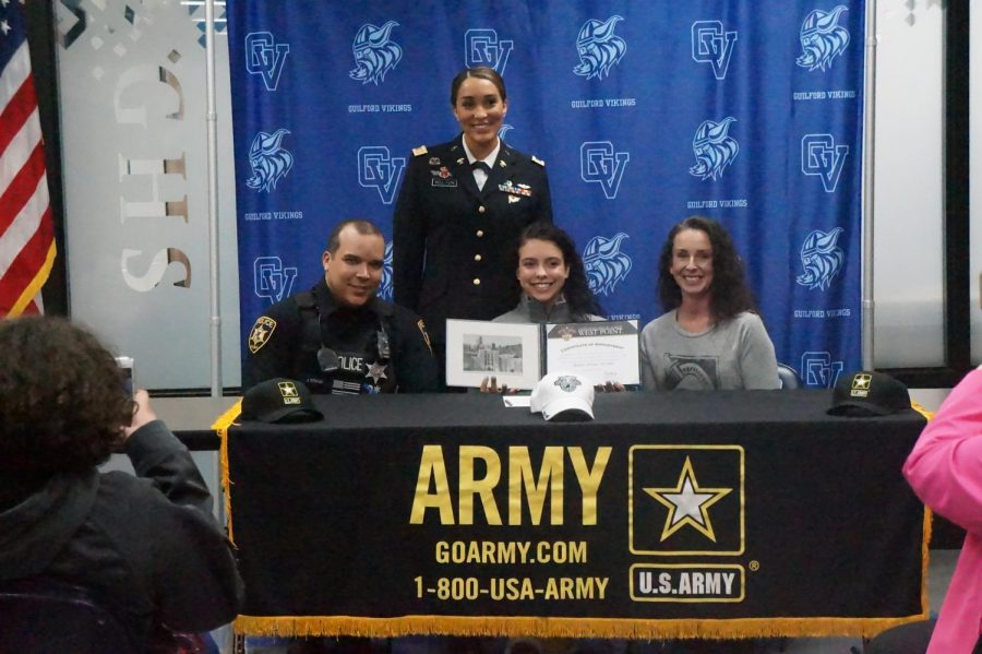 Senior Rylee Strand, flanked by military recruiters and her mother, commits to attending West Point.