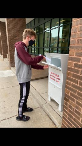 Senior Joe Gibbons places his sealed ballot in an official ballot box.