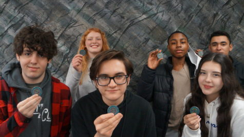 In-person Voyager students show their City of Rockford Challenge Coins. Front row: Gavin Overbey, Ewan Bickford, Alexa Rodriguez-Rodriguez. Back row: Maren Blakeney, Shanyis Jernigan, Jackson Motos.