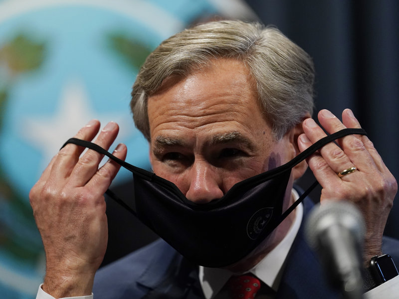 Texas Gov. Greg Abbott dons a mask following a news conference where he provided an update to Texas' response to COVID-19, Thursday, Sept. 17, 2020, in Austin, Texas. (AP Photo/Eric Gay)