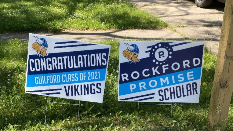 Teachers post graduation signs in lawns